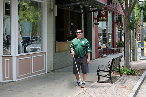 Blind man with cane walking
